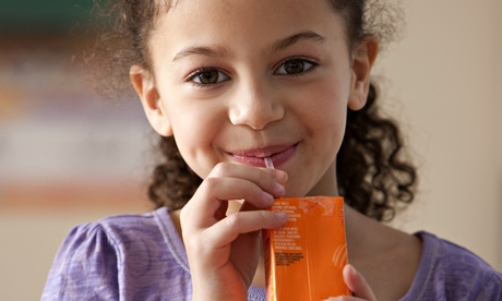 girl drinking juice box for lunch at school