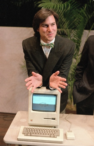 Steve Jobs poses with 1984's Macintosh computer following a shareholder's meeting