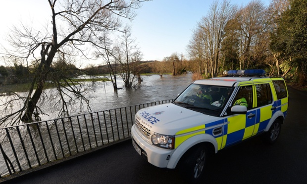 A police vehicle checks a broken barrier along the swollen river Mole in Leatherhead, Surrey.