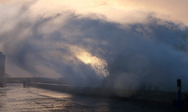 A wave breaks over the seafront at dawn in West Bay during stormy weather in Dorset.