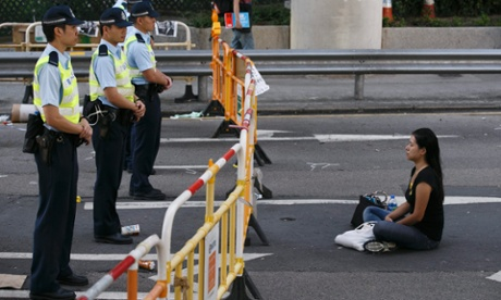 A pro-democracy protester sits in front of Hong Kong police deployed following a removal of outer barricades.