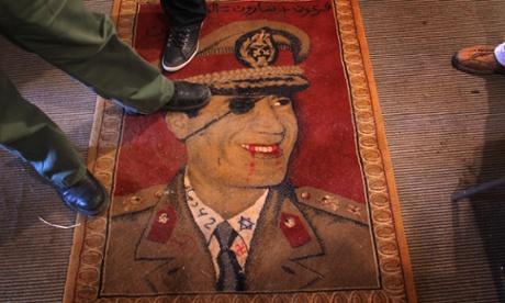 Libyans step on a carpet featuring Libyan leader Muammar Gaddafi on February 25, 2011 in Benghazi, Libya. Gaddafi was killed in October 2011.