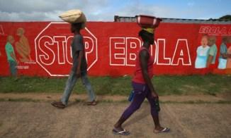 People pass an Ebola awareness mural in Monrovia, Liberia.