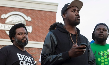 Community activists Montague Simmons and Tory Russell listen as rapper Tef Poe speaks t during a rally in Ferguson.