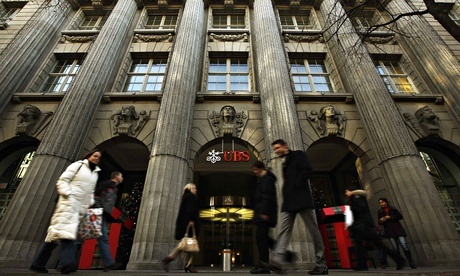People walk in front of a Swiss bank UBS building in Zurich
