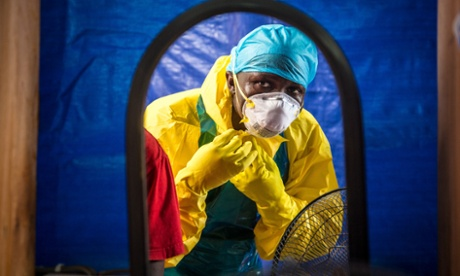 A healthcare worker dressing in protective gear before entering an Ebola treatment center in the west of Freetown, Sierra Leone.