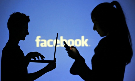 People pose with laptops in front of projection of Facebook logo in this picture illustration