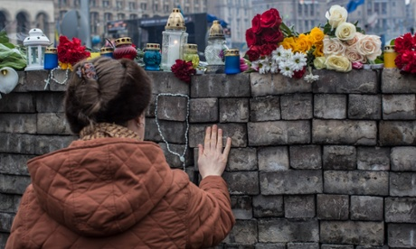 A woman pays her respects at a memorial to anti-government protesters in Kiev, Ukraine