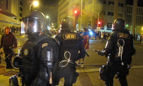 Riot police stand guard in front of protesters in downtown Albuquerque Sunday night.