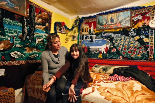 Niculina Fieraru, 39, poses with her daughter Flori Gabriela Dumitrache, 13, in their room in Gura Sutii village, Romania. Niculina Fieraru is unemployed and has two children. She hopes that her daughter will become a seamstress. Flori Gabriela wants to become a pop singer and she hopes to go to high school in a town 14 miles away. Her family cannot afford to pay for it, but a Romanian NGO has offered a scholarship to make this possible.