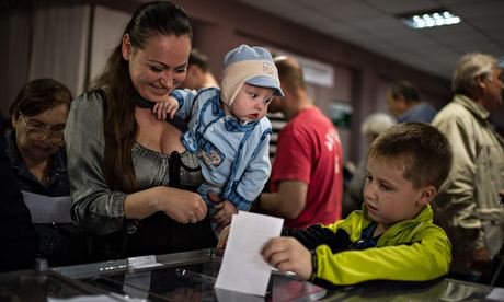 A woman with her children votes in the Ukraine referendum in May 2014
