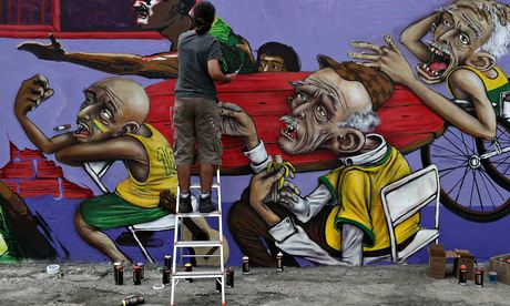 An artist works on a Brazil World Cup-themed mural in downtown Rio.