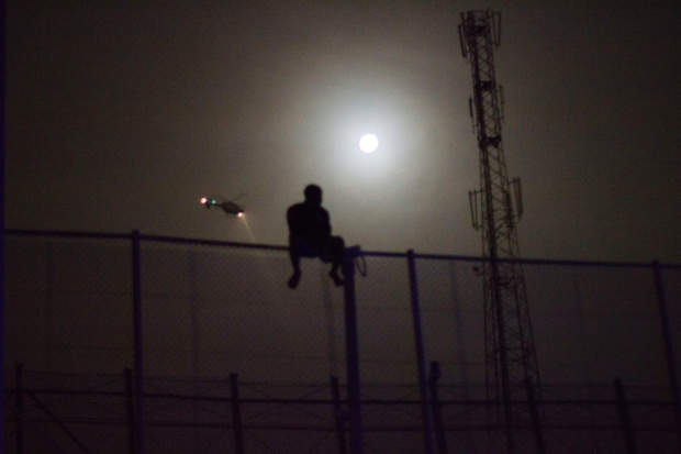 A migrant sits on a fence as a helicopter hovers overhead.