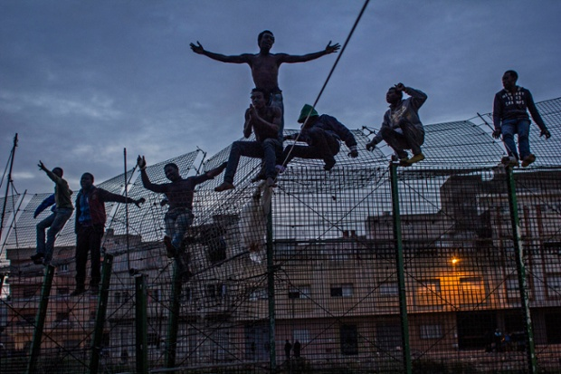 Would-be immigrants stand on a fence near Beni Enza, in March after several hundred launched a dawn attempt to cross into Spain.