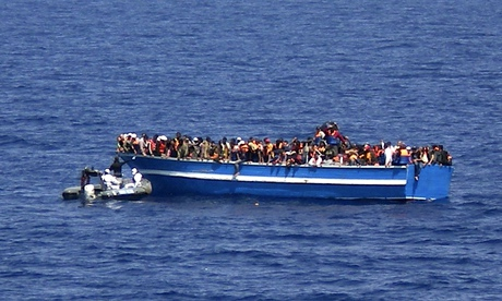 An Italian navy motorboat approaches a boat of migrants in the Mediterranean Sea