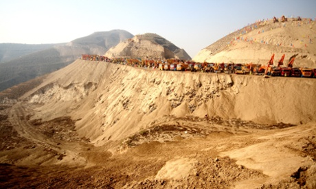 Construction machines are lined up on a mountain during the ground-breaking ceremony for the Lanzhou New Area project in Lanzhou city, northwest Chinas Gansu province, 26 October 2012. In what is being billed as the largest mountain-moving project in Chinese history, one of Chinas biggest construction firms will spend GBP 2.2 billion to flatten 700 mountains levelling the area Lanzhou, allowing developers to build a new metropolis on the outskirts of the northwestern city.
