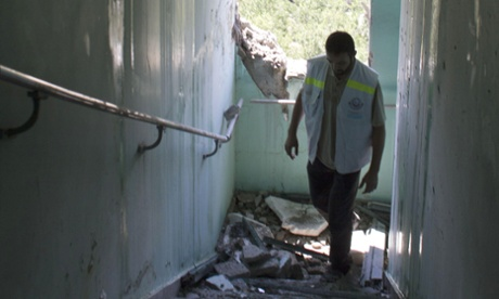 A hospital worker at the Wa'afa  Medical Rehabilitation Hospital in Gaza City stands amongst broken glass and debris from an Israeli shell in the stairwell of the hospital.