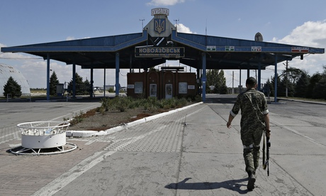 A Pro-Russia rebel walks at the Novoazovsk border crossing point, in eastern Ukraine.