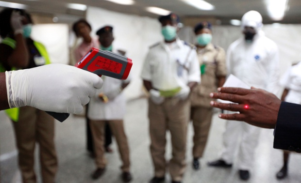 A health official uses a thermometer on a man in the arrivals hall at the Murtala Muhammed International Airport in Lagos, Nigeria.