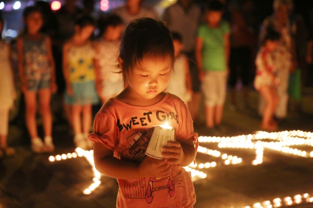A child holds a candle for victims of the Yunnan earthquake in Qinhuangdao, China