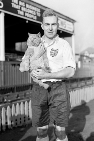 England captain, and Wolverhampton player, Billy Wright holds Tiddles the cat. Tiddles is Brighton and Hove Albion's mascot and the England players were at their ground training ahead of their match against Italy.