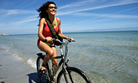 A young woman cycling on a beach, smiling