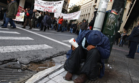 A man begs on a street in Athens