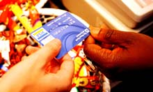A RBS Visa debit card being handed to a shop assistant