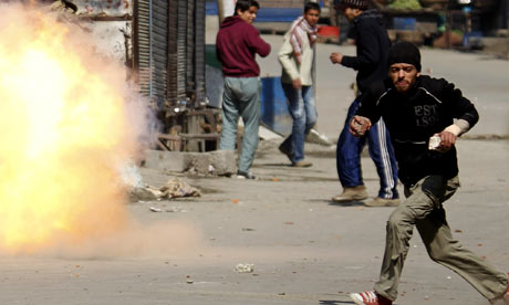 Kashmiri protester runs as tear gas shell explodes during anti-Indian protest in Srinagar