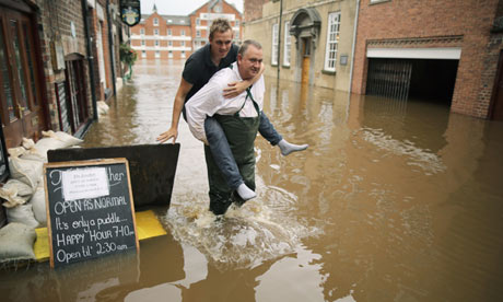 A man carries a a freind through floodwaters in York