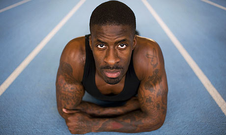 Dwain Chambers looks at the tattoos covering his body as if the blue