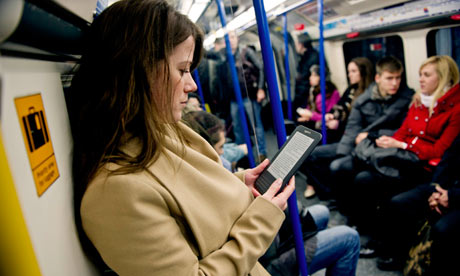 A young woman reads a Kindle on the tube