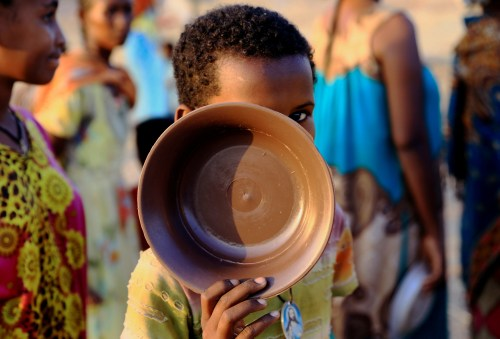 An Ethiopian child who fled war in Tigray region carries his plate as he queues for wet food ration at the Um-Rakoba camp, on the Sudan-Ethiopia border in Al-Qadarif state