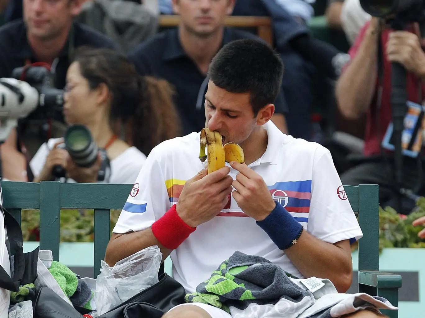 Novak Djokovic tucks into a healthy banana during a break between games