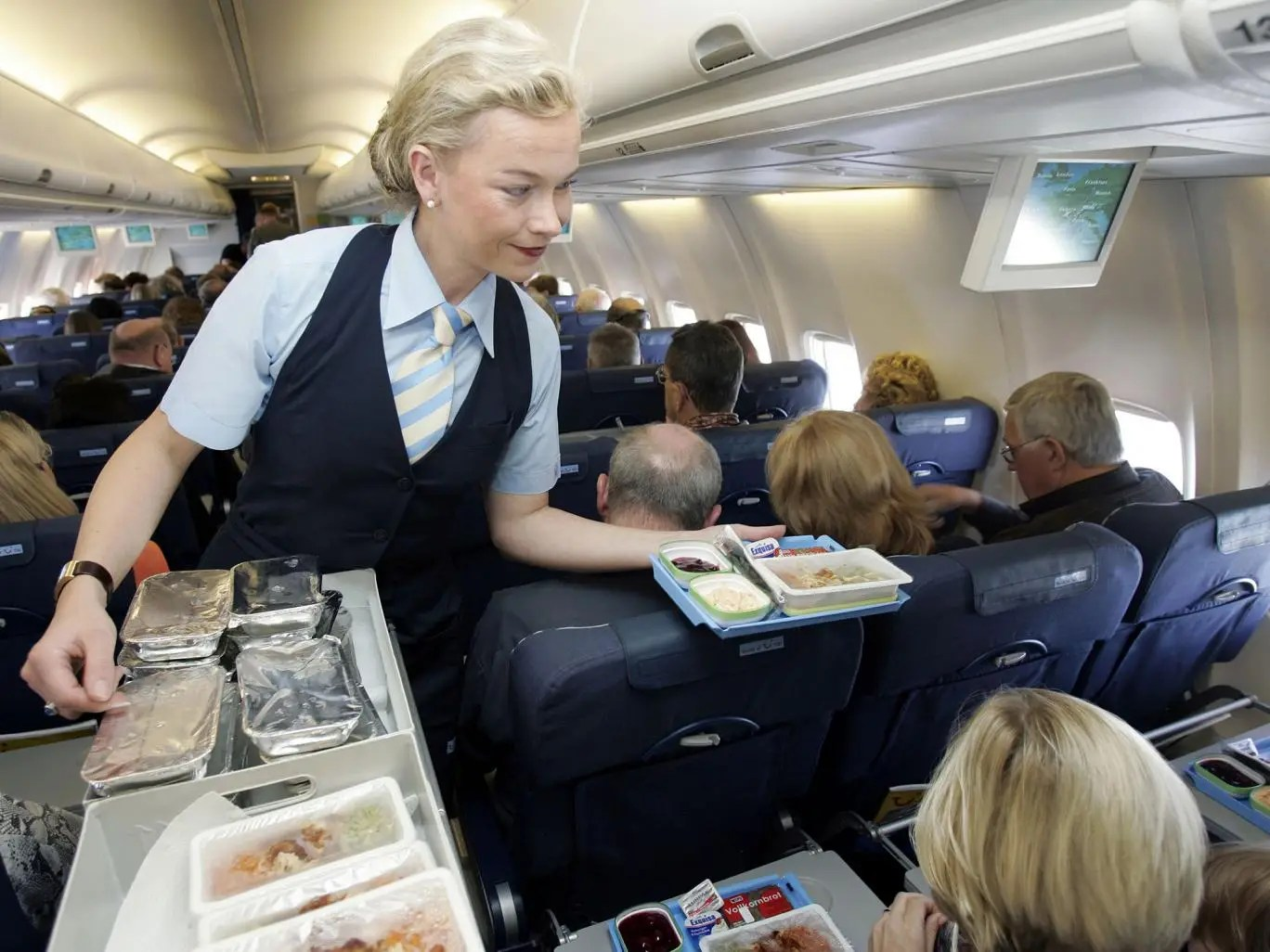 Flight attendant serving in the cabin of an aeroplane