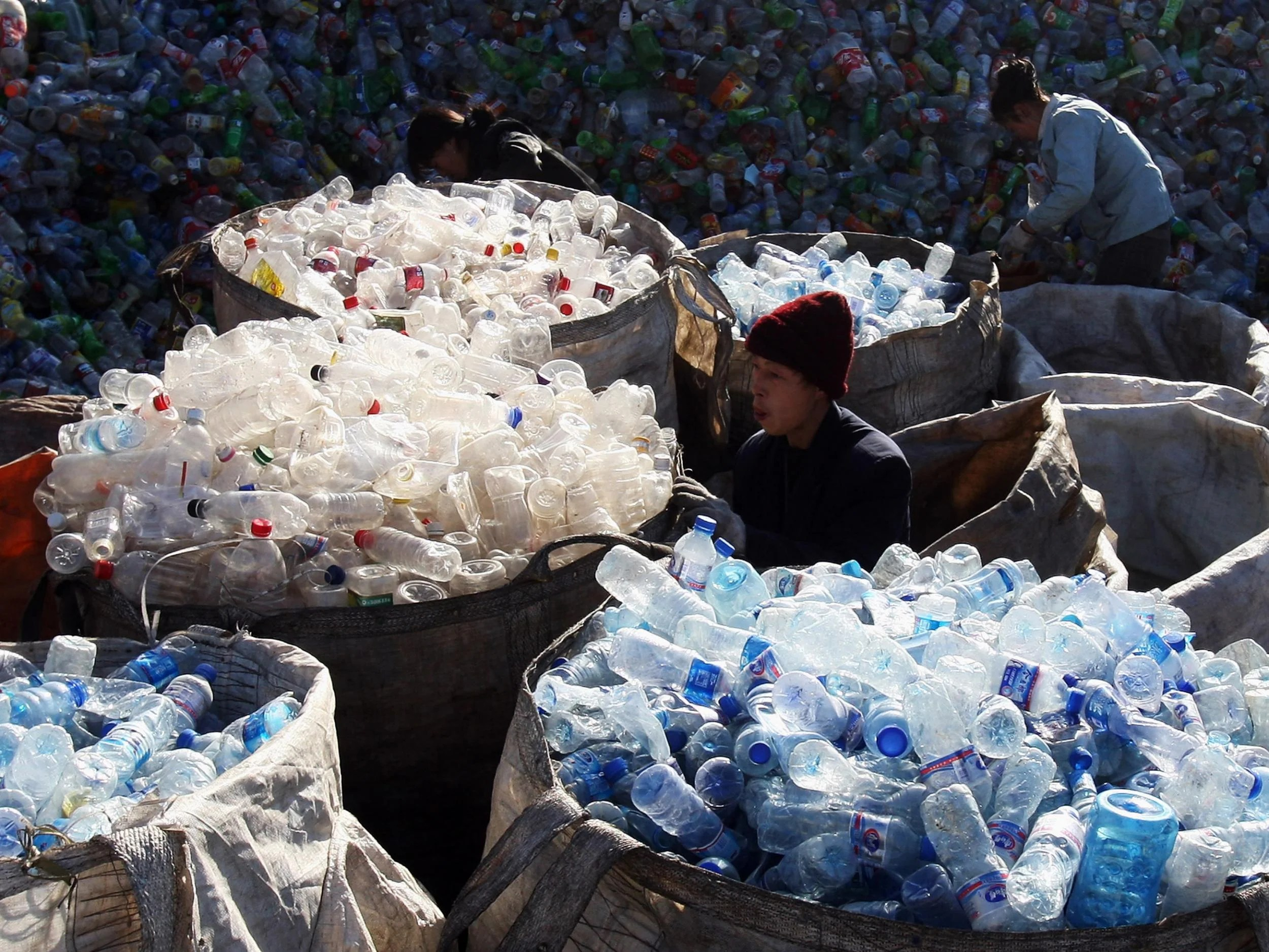 Labourers collect assorted plastic products from a garbage pile at a recycling centre on the outskirts of Beijing