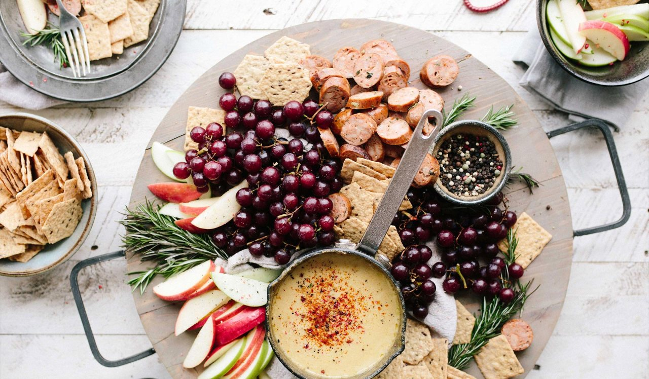 An aerial shot of a wooden platter with hummus, red grapes, crackers, cheese, apple slices, sliced meat and a bowl of peppercorns.