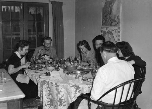 Several  young adults eating at large dinner table.