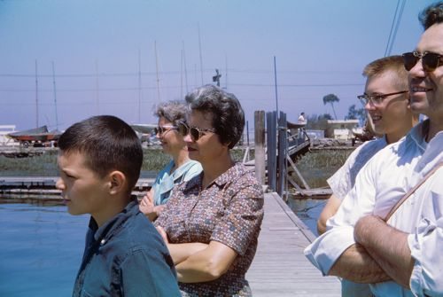 Three adults and two teen boys watching someone sailing.