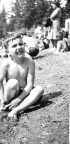 Very young boy in suit sitting on beach frowing