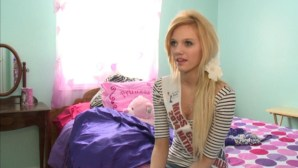 Pretty girl with Beauty Pagent sash sitting on bed
