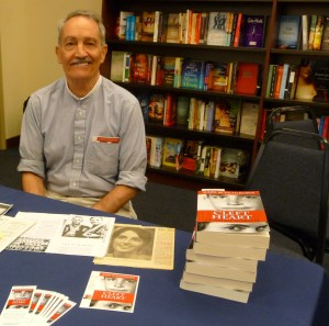 Karl Schonborn sitting at bookstore table w stack of books.