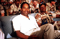 Black man, OJ Simpson, seated in white shirt & slacks.
