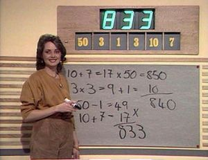 Carol Vorderman at white board show demonstrating  math skill