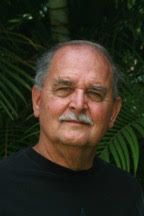 Older man with greying hair and mustache posed before palm leaves.