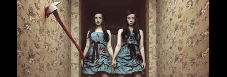 The SOSKAS twin sisters hold hands in a hallway with a bloody axe imbedded in a wall.