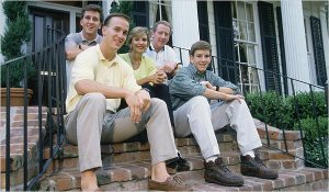 Cleft palate P Manning (l) sitting on steps with family or origin, incl QB dad (ctr) & QB bro (r).