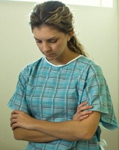 Young woman with bowed head and folded arms in hospital gown.