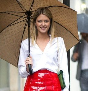 Nice figured, smiling, healthy haired woman wearing red. holding umbrella.