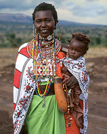 3/4 shot of Masai Woman Meeyu Sale with baby. Wearing her finest per photographer Jack-z' request. Less bullying?